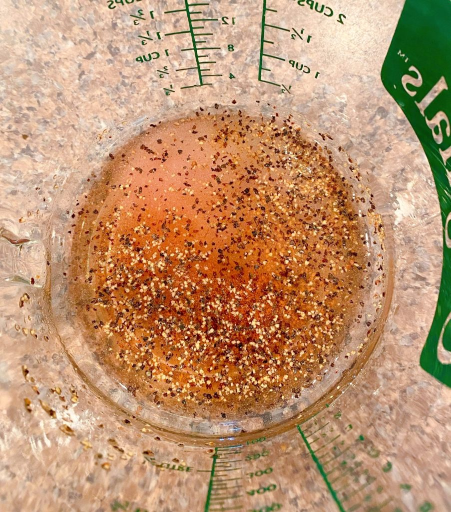 Red wine vinegar, salt, pepper, and sugar for mayo dressing in measuring cup.