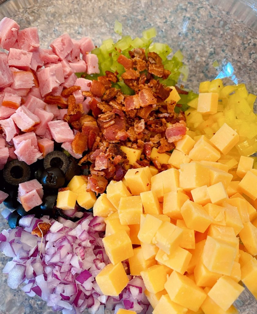 Crumbled bacon and diced cheddar cheese in bowl with other salad ingredients.