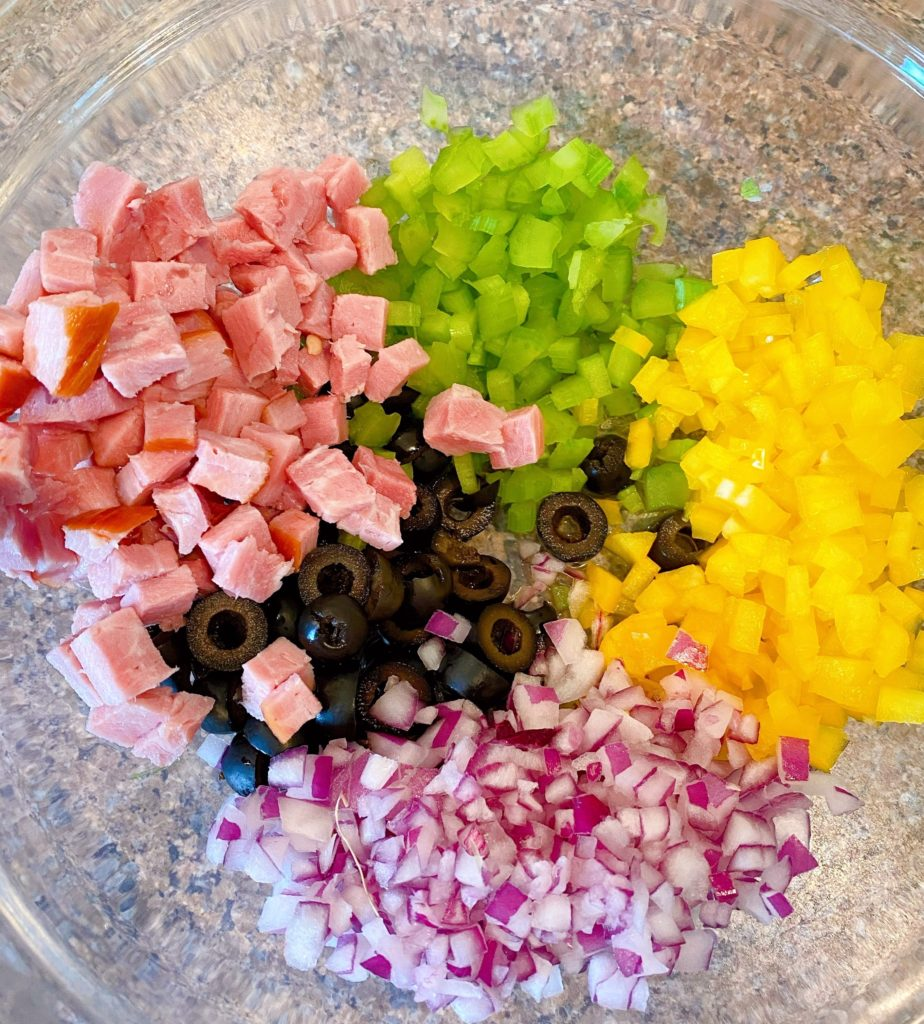 Chopped pasta salad ingredients, ham, red onion, olives, yellow pepper, celery.