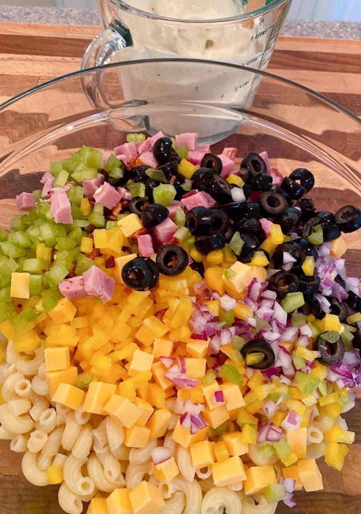 Adding salad ingredients to the macaroni.