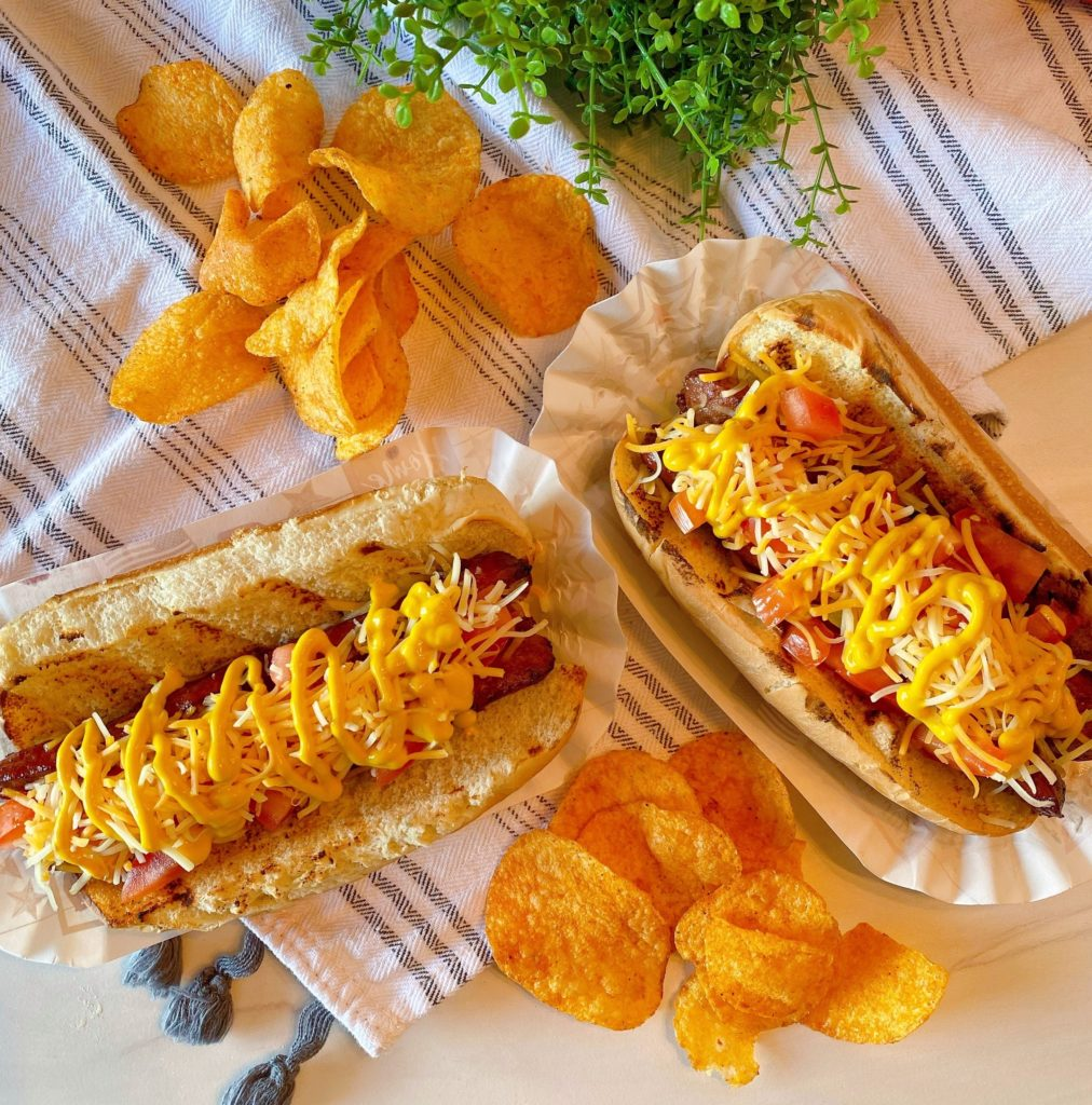 Polish Dogs with chips on a table.