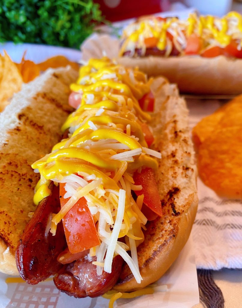 Grilled Sunday Polish Dog with toppings.