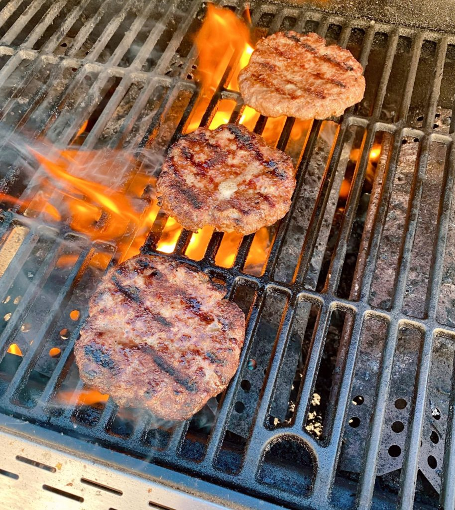 Grilled Hamburgers on the BBQ with flames.