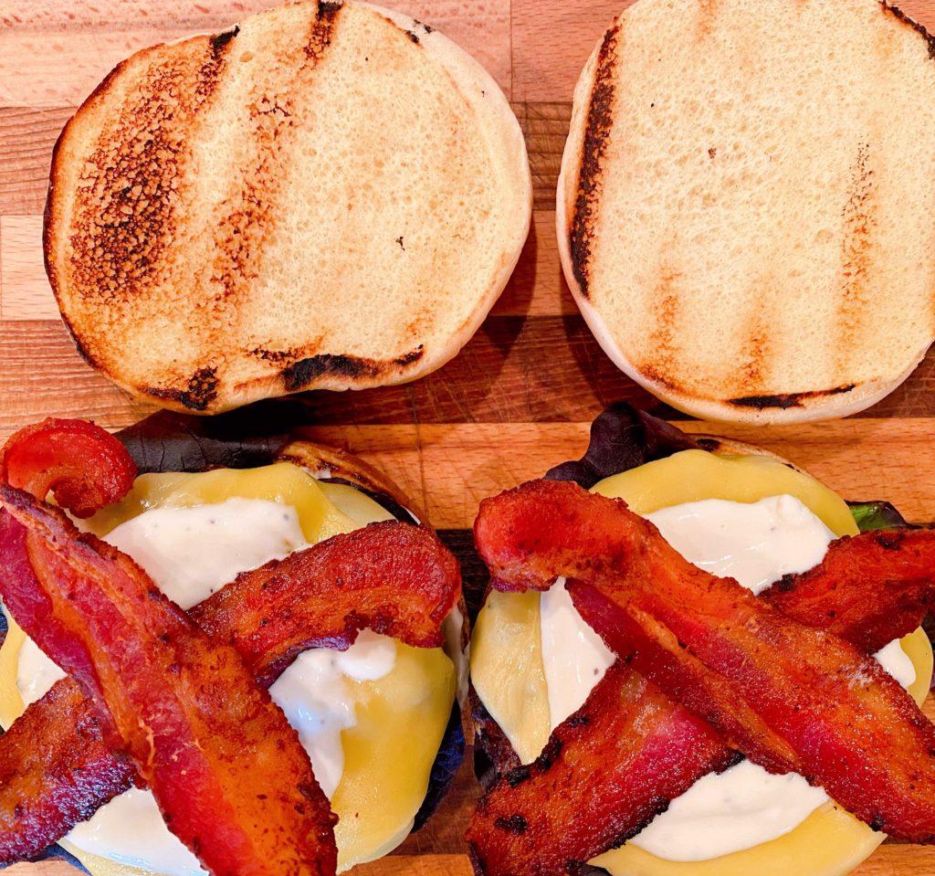Adding Bacon to burger.