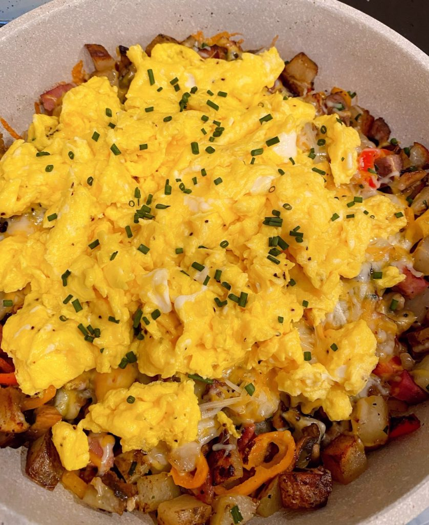 Adding scrambled eggs to cooked skillet veggies and meats. Topped with more chopped chives.
