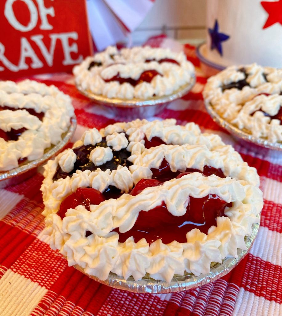 Mini No Bake Patriotic Cheesecake Pies with cherry and blueberry pie filling decorated like a flag on a red and white plaid cloth.