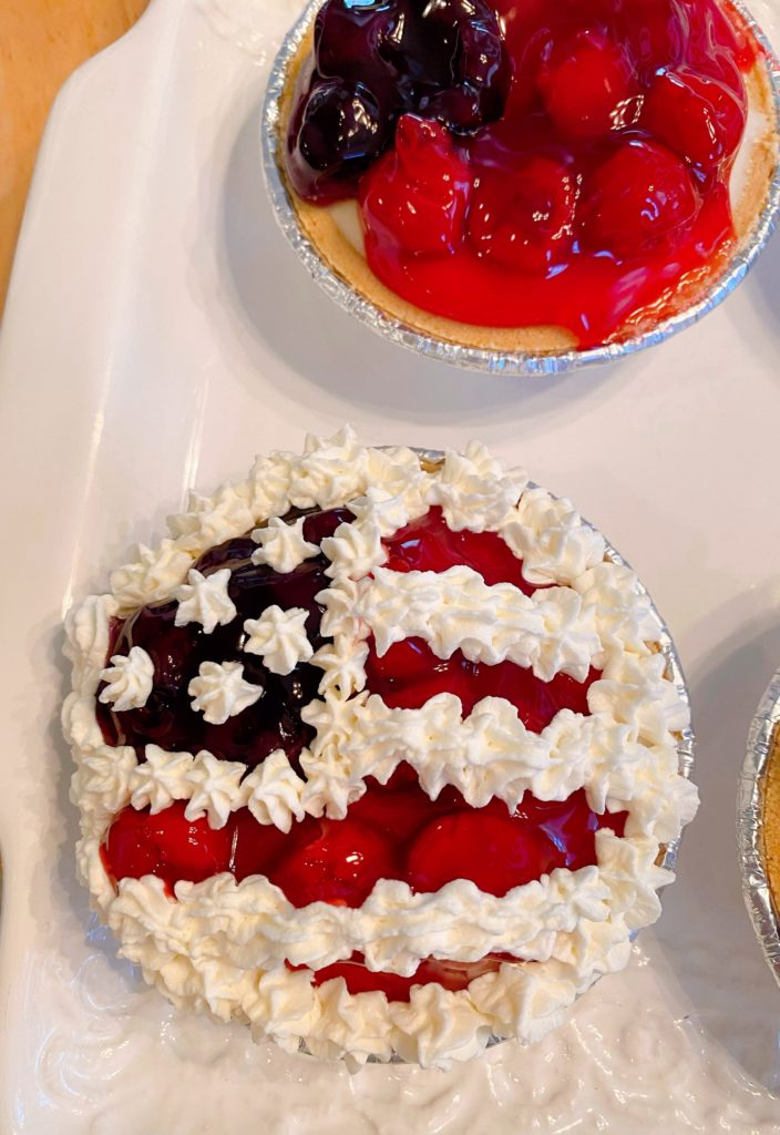 Mini pie with whipped cream piped onto the pie to create the stars and stripes.