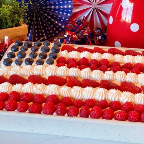 Red, White and Blue Poke Cake with fresh berries decorated like an American Flag.
