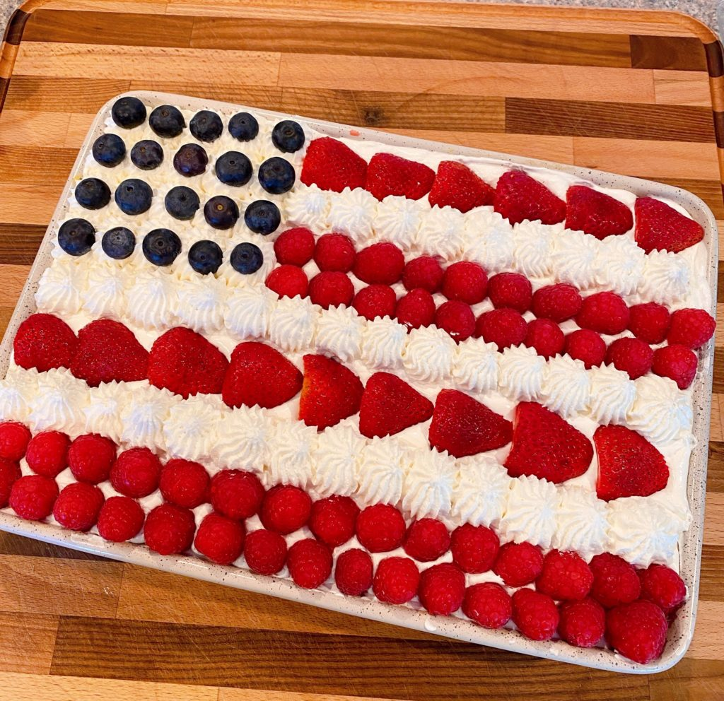 Adding berries to the top of the cake to create a flag.