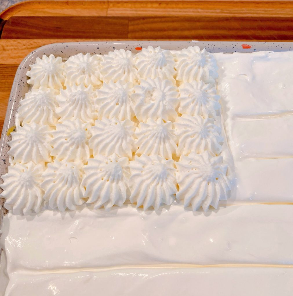 Cake with lines drawn on the top and whip cream stars.