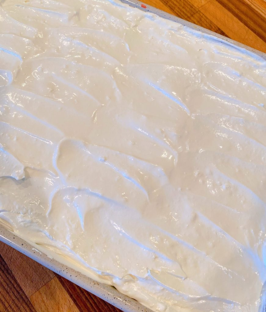 Cool Whip spread over the top of the cake ontop of the pudding.