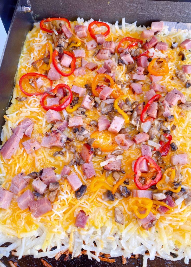 Adding toppings to hash brown omelets.