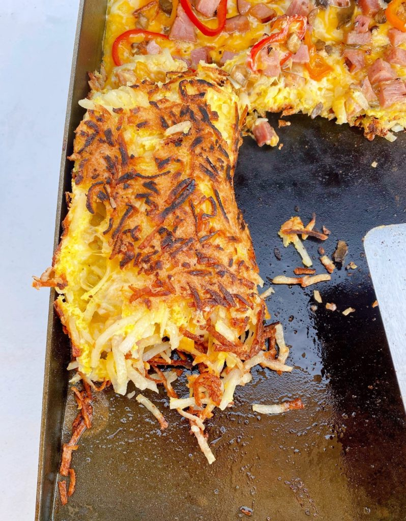 Rolling the hash brown omelet.