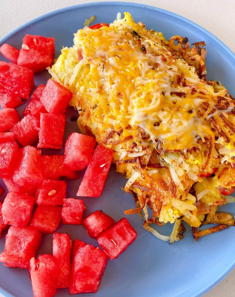 Breakfast Loaded Hash Brown Grilled  Omelet on a plage with fresh cut up watermelon.