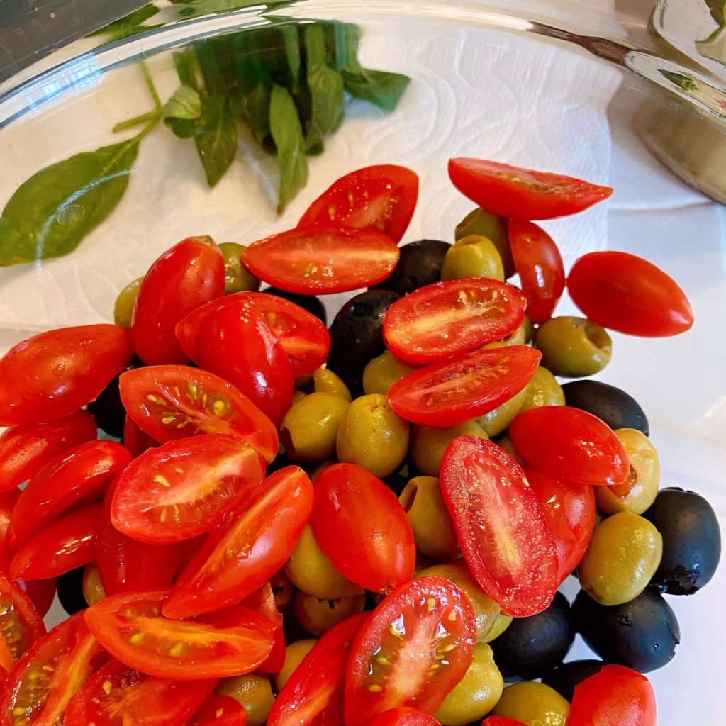 Adding sliced grape tomatoes to olives in large bowl.