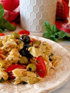 Muffuletta Olive Pasta Salad close up photo on a white plate with fresh basil surrounding it.
