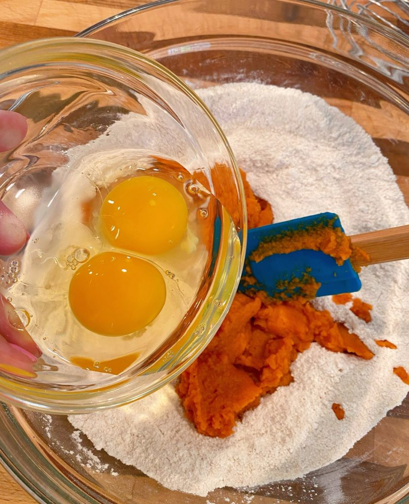 Adding pumpkin and eggs to dry ingredients.