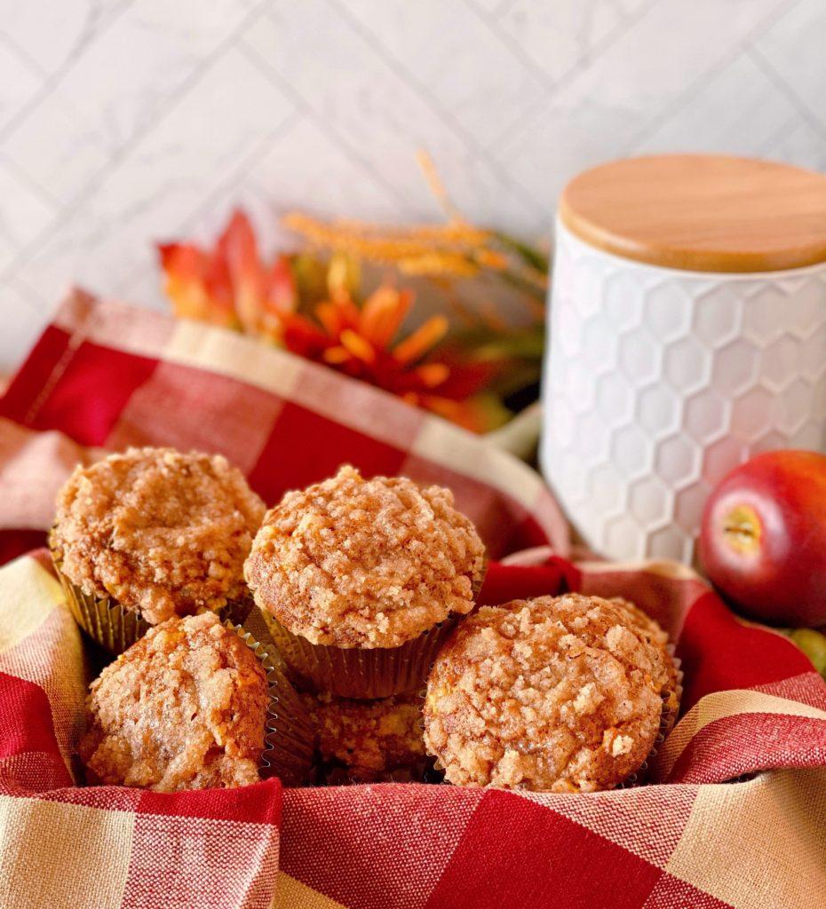 Basket full of Pumpkin Apple Streusel Muffin on a plaid napkin.