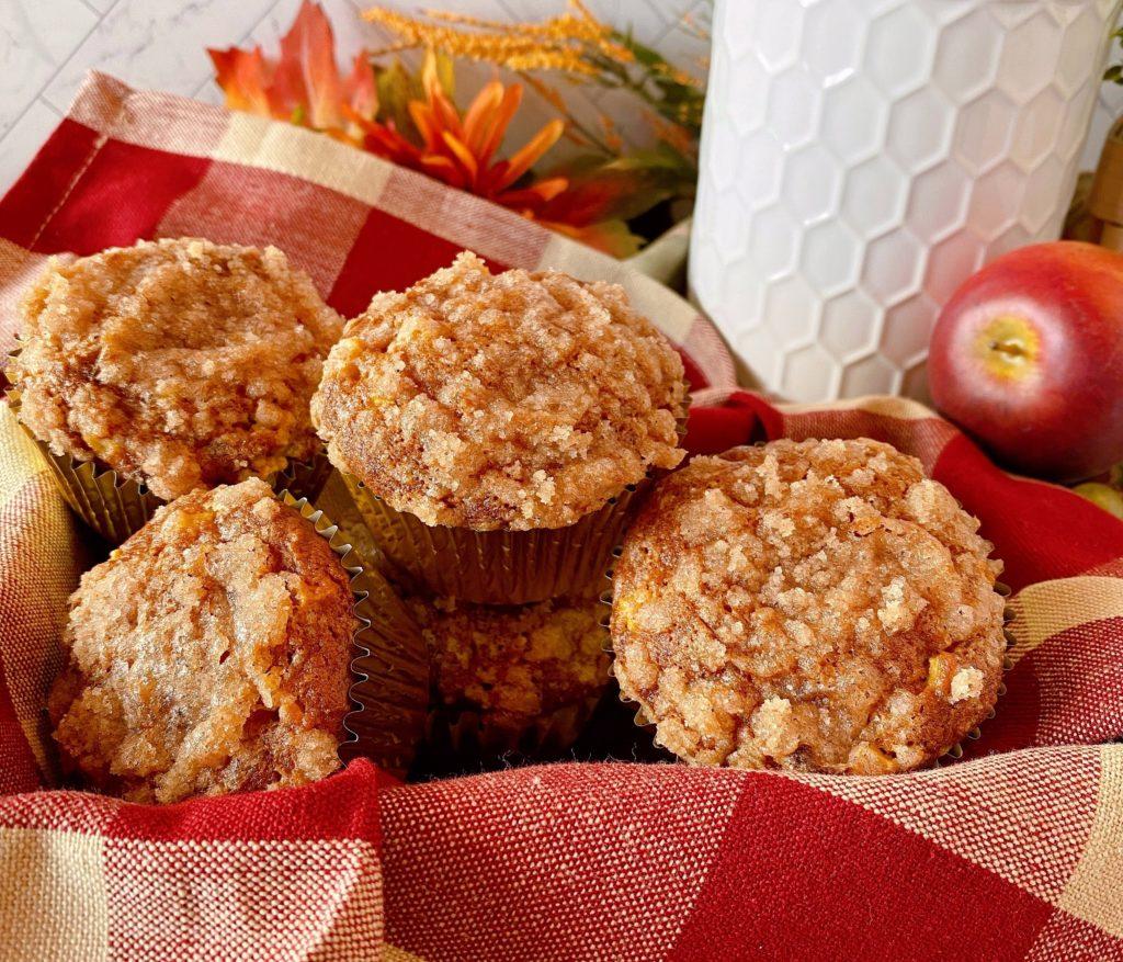 Pumpkin Apple Streusel Muffins on a plaid napkin in a basket.