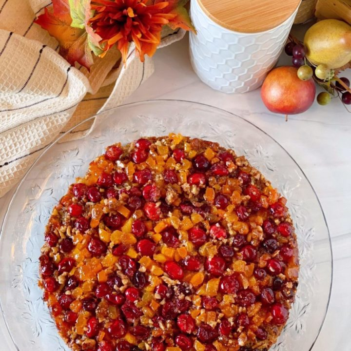 Overhead photo of Cranberry Upside down cake on a crystal cake plate on a white counter top.