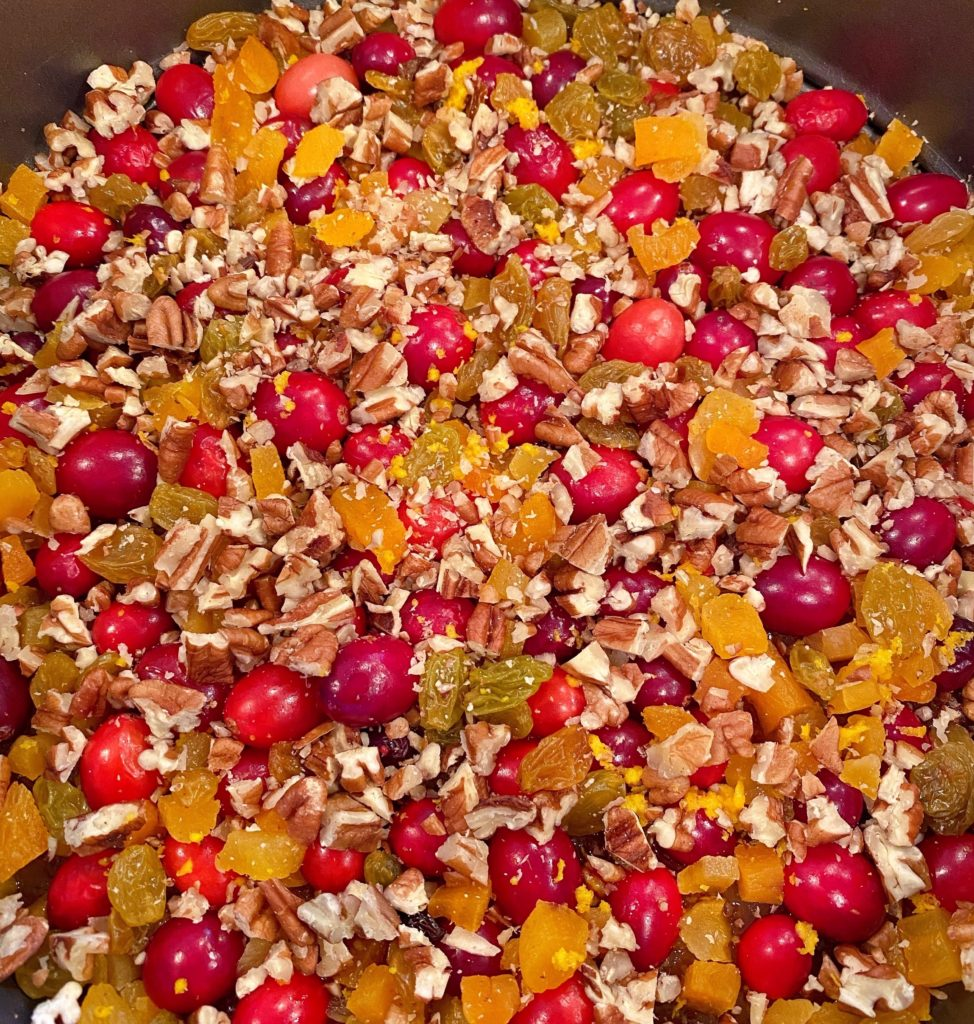 Adding chopped nuts to cake top with cranberries.