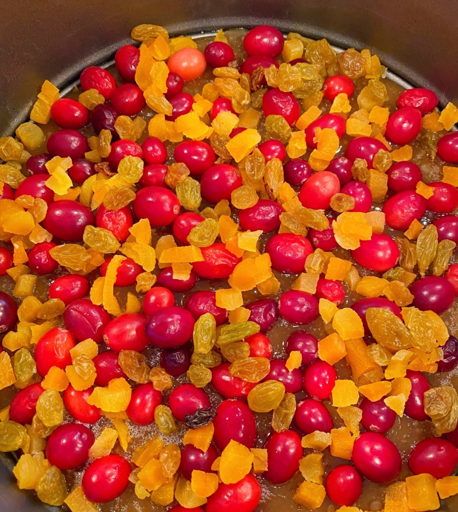 Apricots and Golden Raisins added to cranberry topping in springform pan.
