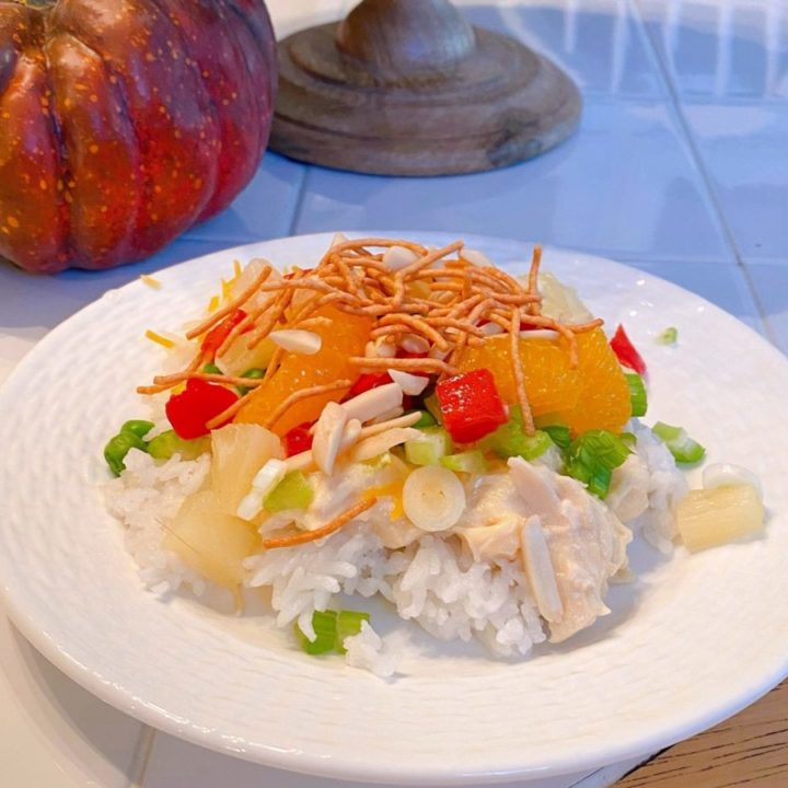 Hawaiian Haystacks on a white plate on a kitchen table with Fall decor around it.