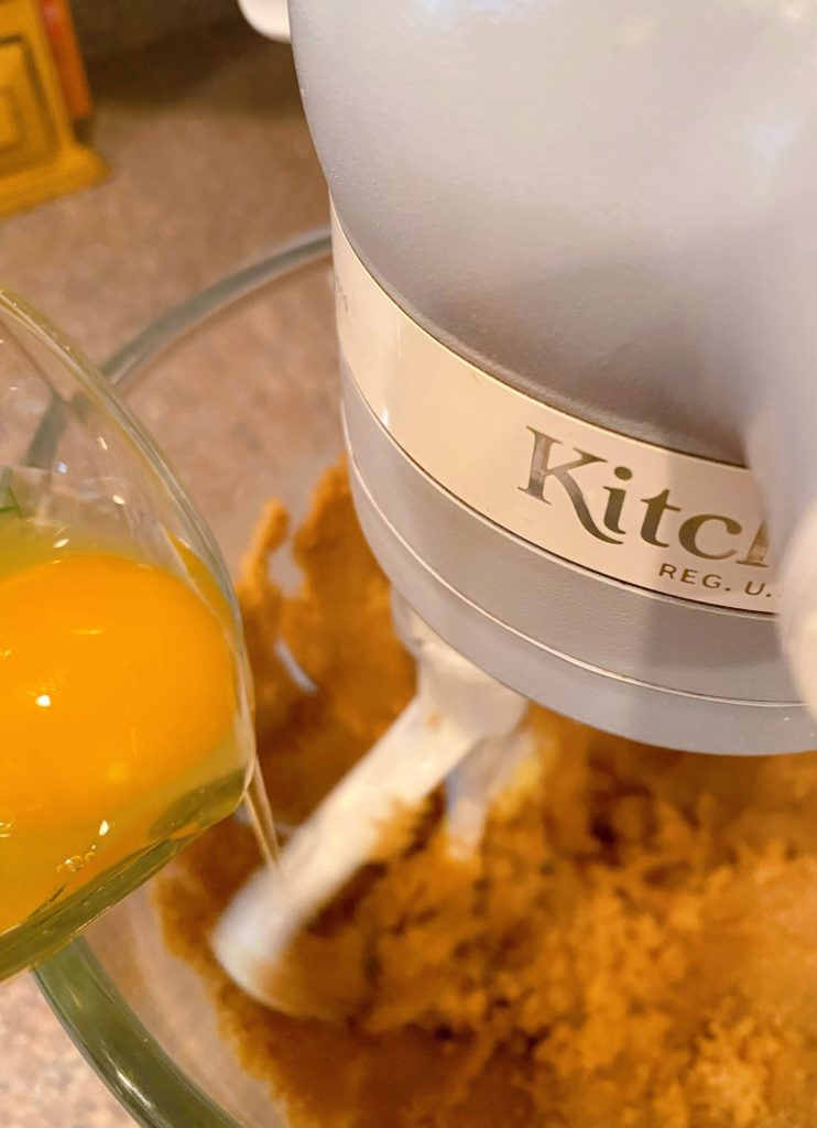 Adding eggs to creamed butter and brown sugar.