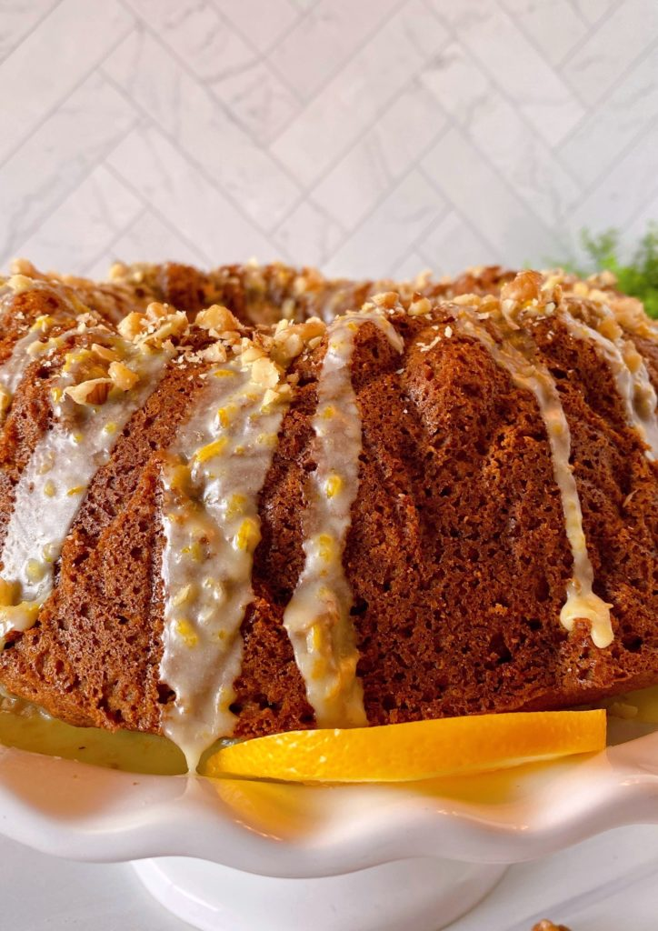 Glaze drizzled over cake with sprinkled chopped walnuts on top.